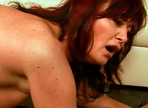 Redhead mature woman bends over for a big fuck machine